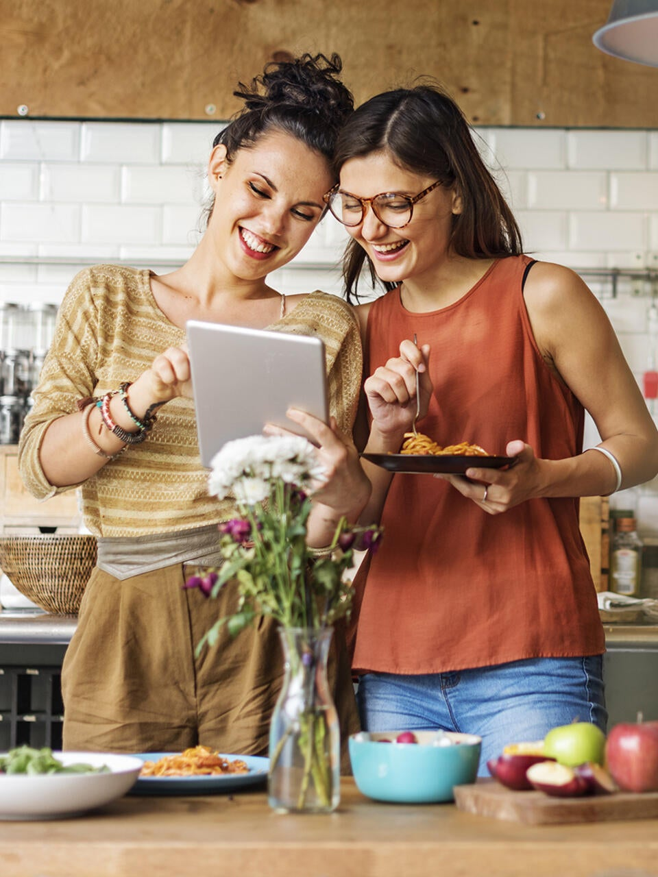 Two smiling young women use a tablet in a modern kitchen.