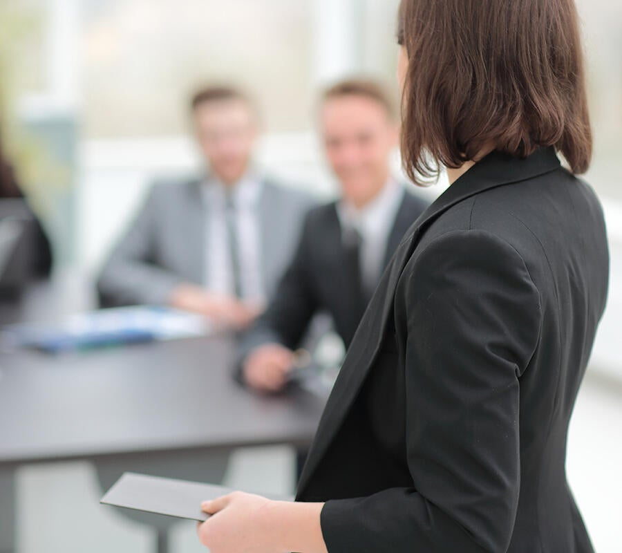 A woman in a blazer presents to a room full of businessmen.