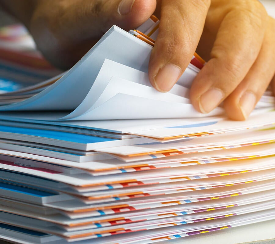 A hand leafing through a stack of corporate documents.
