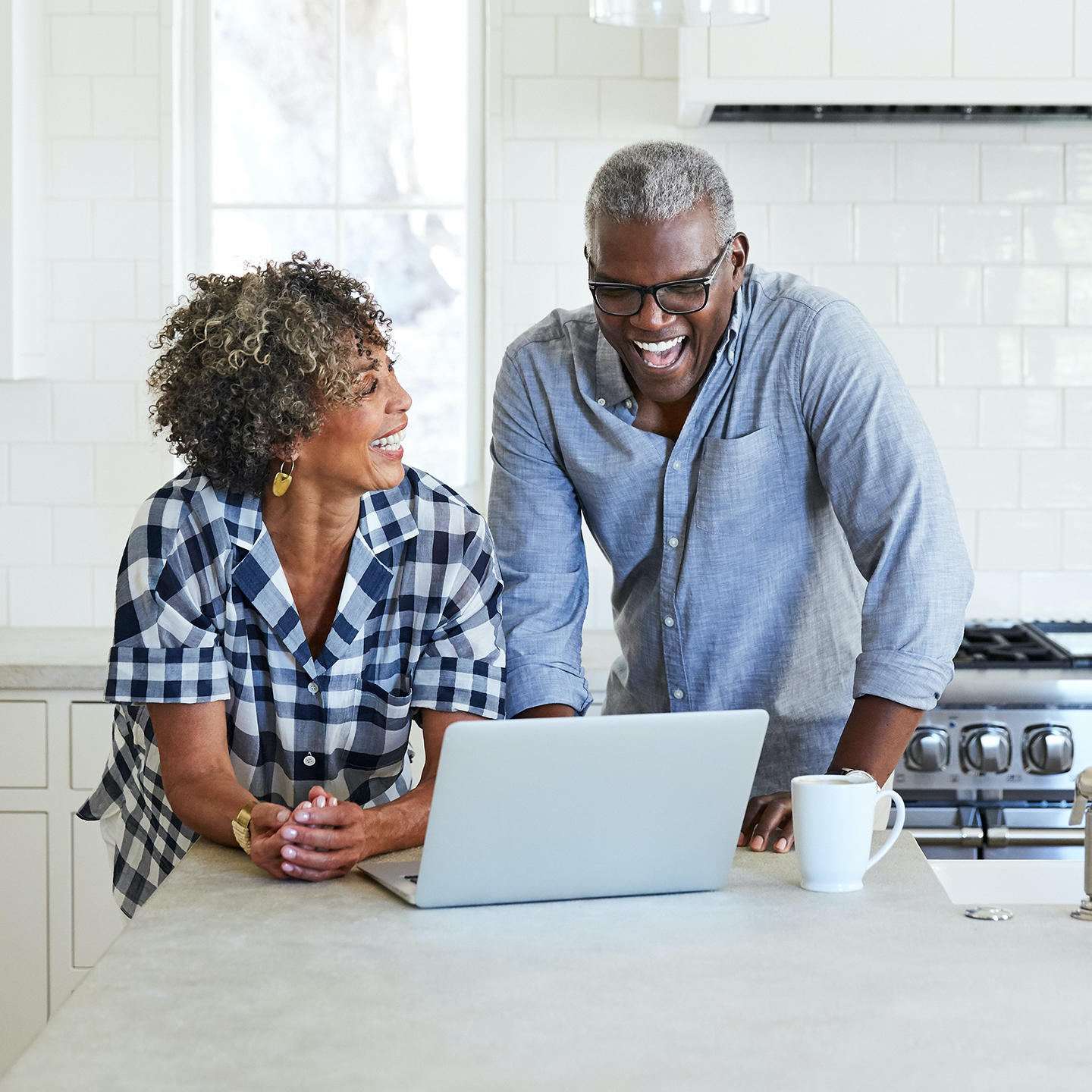 A middle-aged African-American woman and man using a laptop in a modern kitchen.
